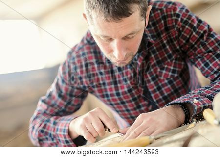 Engravershot of a male carpenter working on a project in his workshop.