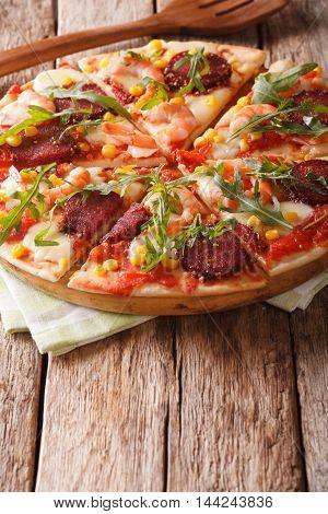 Italian Pizza With Salami, Shrimp, Corn, Mozzarella And Arugula Close-up. Vertical