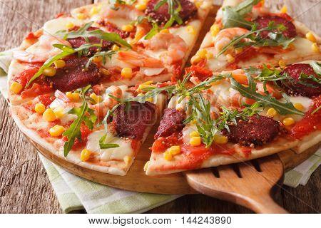 Sliced Pizza With Shrimp, Salami, Cheese And Arugula Close-up. Horizontal