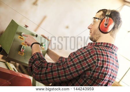 Carpenter with automatic circular saw. He has protective glasses.