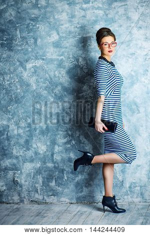 Fashionable lady in elegant dress and pin-up hairstyle posing at studio. Beauty, fashion concept.