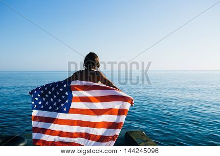 Rear view of unrecognizable young woman holding american waving flag at coastline against of sunny bright sea