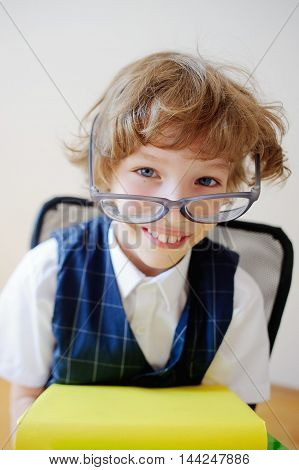 Disheveled little schoolboy looks into the camera and smiling. He has a great mood. Huge glasses fall from his face. This is a primary school pupil.