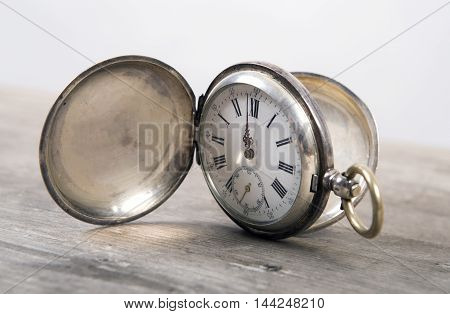 Old iron pocket-watch on wooden background. Time concept