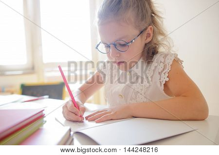 Cute little schoolgirl in glasses something diligently writes in a notebook. Girl sitting at the desk in the classroom. She is elementary school student.