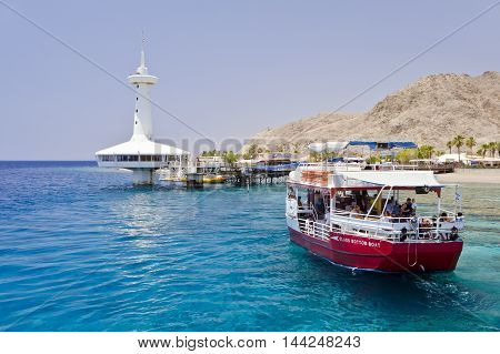 Pleasure tourist boat at coral reef and underwater observatory near Eilat - famous resort city in Israel