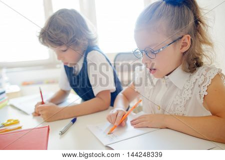 Cute little schoolgirl in glasses something diligently writes in a copybook. Girl sitting at the desk. Next to the schoolgirl sits her classmate. They are students of elementary school.
