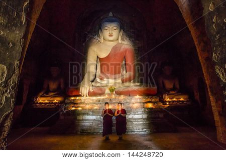 Bagan Myanmar November 13th 2014: Young monk praying in front of a statue of Buddha