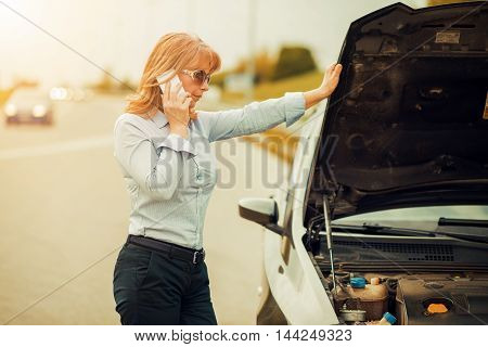 Woman with car trouble in the middle of the street after car breakdown.