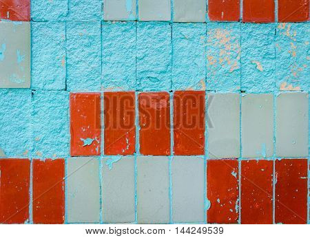 Wall covered by old brown and gray tiles with empty fragments painted blue, peeled and scratched, grunge background