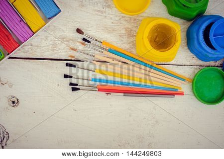 Tools for creative work on a white wooden background. Watercolor paintbox. Color paints with paint brushes and plasticine. Back to school. Kids painting concept. Children art. Top view. Copy space.