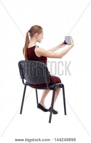 back view of woman sitting on chair and looks at the screen of the tablet.  Rear view people collection.  backside view of person.  Isolated over white background. A girl in a burgundy dress sitting