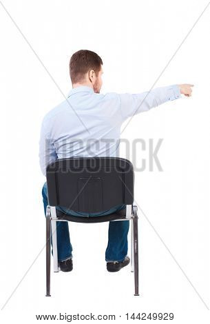 back view of young business man sitting on chair and pointing. Rear view people collection.Bearded businessman in white shirt sitting on chair and pointing her finger.