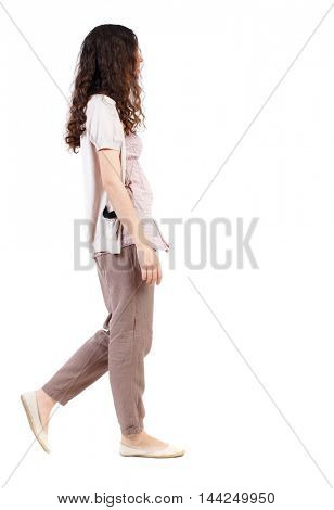 back view of walking  curly woman.  backside view of person.  Rear view people collection. Isolated over white background.Long-haired curly girl goes sideways.