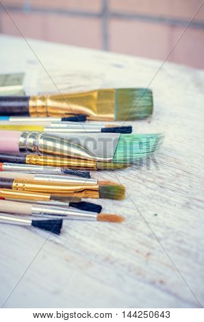 Artist paint brushes on white wooden background. Brush, paint, artistic. Tools for creative work. Watercolor paintbrush. Back to school. Paintings Art Concept. Selective focus. Copy space.