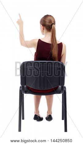 back view of young beautiful  woman sitting on chair and pointing.  girl  watching. Rear view people collection. A girl in a burgundy dress sitting on a chair and presses his finger on the button.