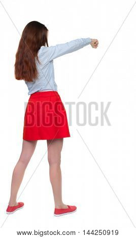 skinny woman funny fights waving his arms and legs. Isolated over white background. Long-haired brunette in red skirt boxing.