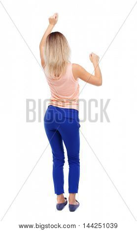 back view of dancing young beautiful  woman. girl  watching. Rear view people collection.  backside view of person.  Isolated over white background. Blonde in blue pants waving dancing raising his