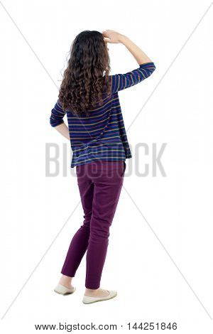 back view of standing young beautiful  woman.  girl  watching. Rear view people collection.  backside view of person.  Long-haired curly girl in a blue blouse looks away his hand to his eyes.