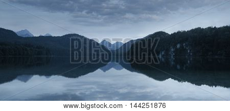 Alpsee panoramic view of a calm lake after sunset