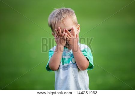 Little boy playing peek-a-boo in summer park