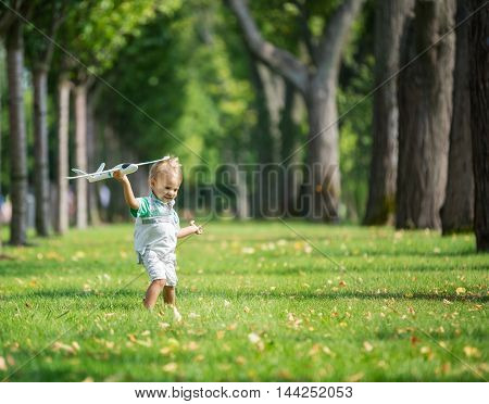 Toddler boy playing with toy glider in park on summer day