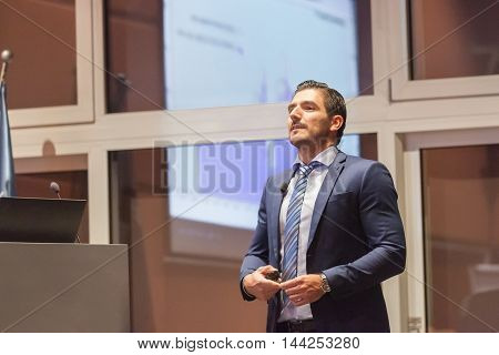 Speaker giving talk on podium at Business Conference. Entrepreneurship club. Horizontal composition.