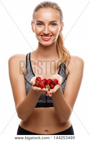 Young beautiful sportive girl posing, holding strawberries over white background. Copy space.