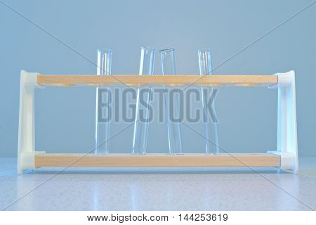 Four empty glass Test Tubes in a Rack. Grey background.