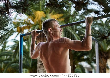 Fitness sport exercising training and lifestyle concept - young man doing pull ups on horizontal bar outdoors. Healthy lifestyle.