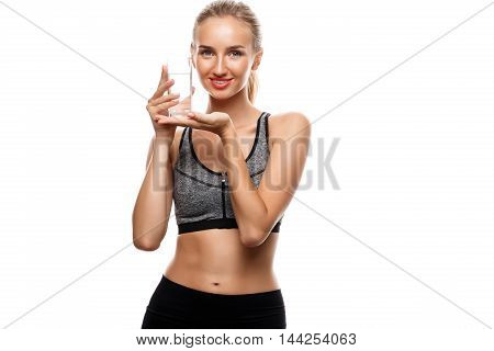 Young beautiful sportive girl posing, holding glass of water over white background. Copy space.