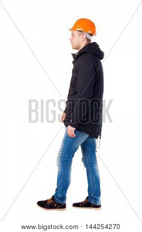 Back view of walking engineer in helmet. Isolated over white background. Engineer in warm clothing thoughtfully goes right
