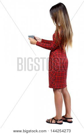 back view of standing young beautiful woman and using a mobile phone. girl watching. girl in red plaid dress standing sideways and looking at the tablet.