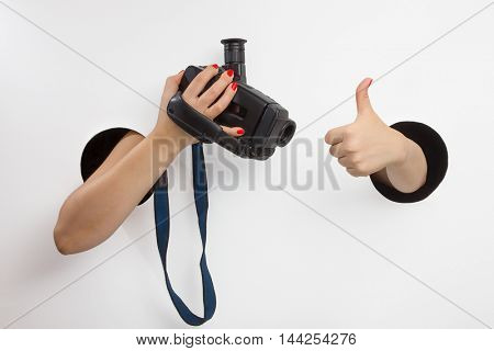 Female hands through the holes on a white background are holding a retro camera