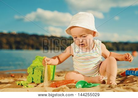 Cute baby boy playing with beach toys on tropical beach.