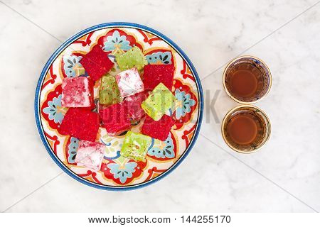 Turkish delights and tea on marble background