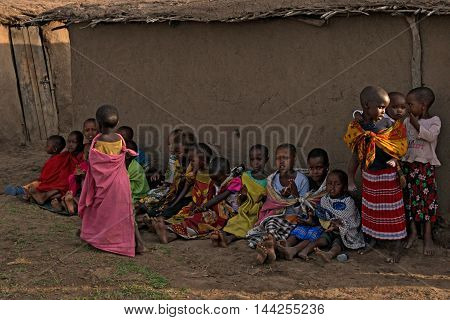 MAASAI VILLAGE, KENYA - JANUARY 2 2015: Children of maasai tribe seat on the ground near their houses. Problems of African children are very sharp nowadays and have actual humanitarian significance