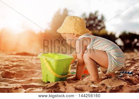 Baby playing on the sandy beach near the sea.