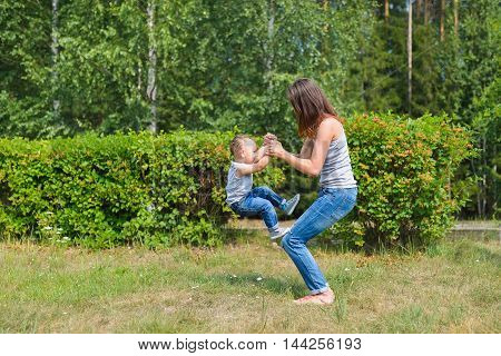 mother and son have fun playing in park. Littkek kid making steps upwards over moms legs.