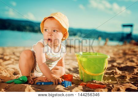 Baby boy playing with toys on the beach.
