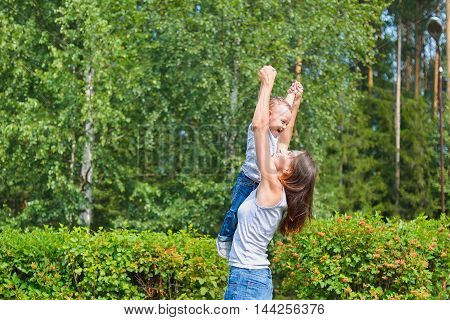 Happy family having fun outdoors. Mother holding son in the air like airplane.