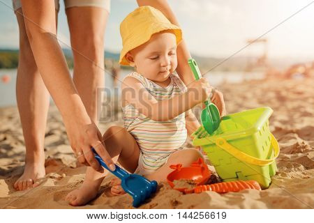 Mother playing with her little son on the beach.