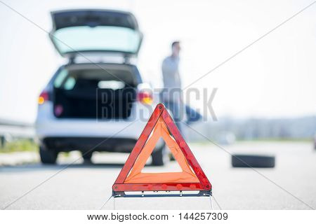 A young man with a silver car that broke down on the road.He has set up a warning triangle.He is waiting for the technician to arrive.