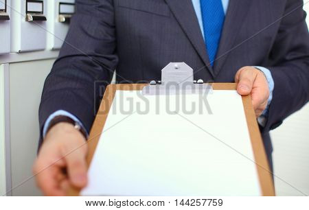 a stack of papers on the desk with a computer.