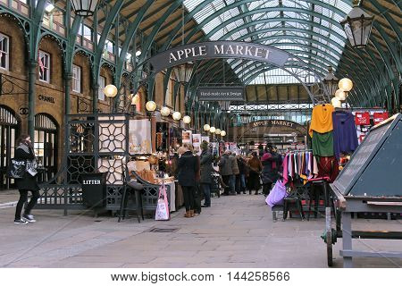 LONDON UK - February 10: Famous Apple Market inside Covent Garden with people walking around and shopping in London UK - February 10 2015; The Apple Market is the permanent Market at Covent Garden that happens seven days a week.