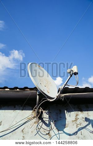TV satellite dish aimed in the blue sky