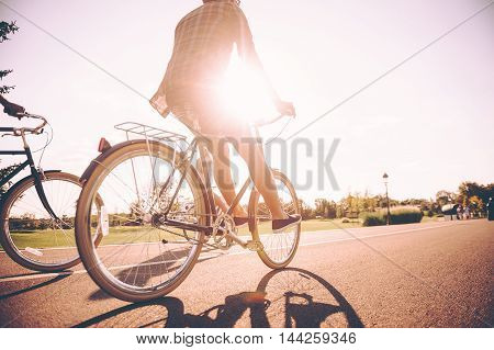 On the way to sunrise. Low angle view of young man riding bicycle together with his friends along the road