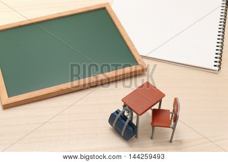 Miniature blackboard, notebook, desk, and school bag on wood.