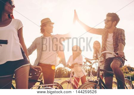 High five! Low angle view of cheerful young people standing near their bicycles on the road while two men giving high five