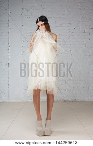 Woman hides her face behind her skirt tutu full body standing in white interior